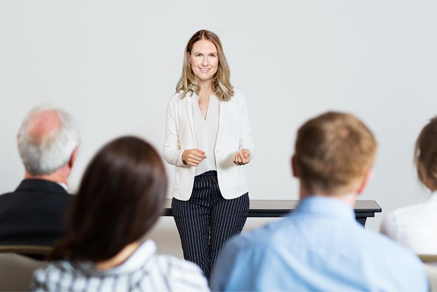Frau spricht vor Mitarbeitern